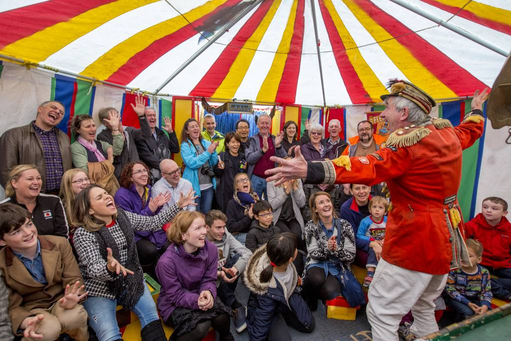 A man in circus costume performing to an audience in a colourful tent