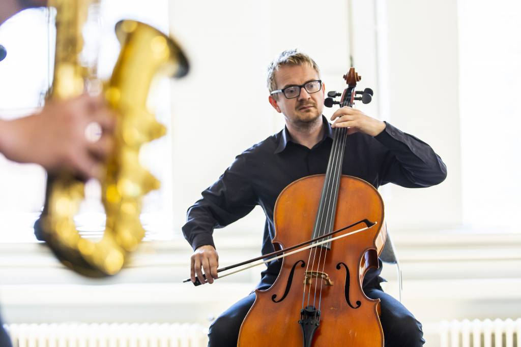 A man with glasses and a black shirt playing a cello and aomone playing a saxaphone in the foreground.