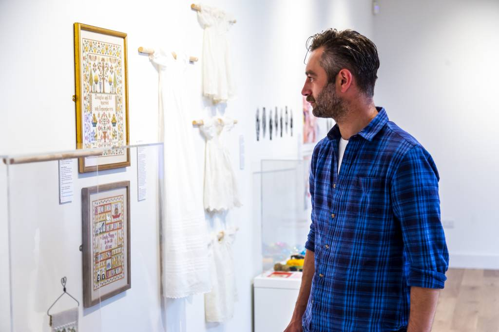Man with short dark hair and a blue and black checked shirt looking at a framed embroidery picture in the exhibition gallery.