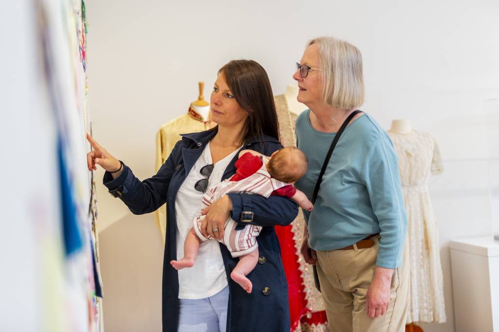 Two women look at the gallery display. One of them is holding a baby.
