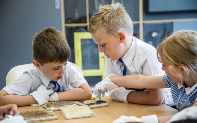Three children handling museum objects whilst wearing white gloves