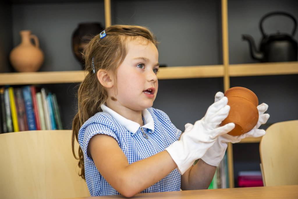 Young girl wearing a blue gingham school uniform dress is wearing white gloves and handling a clay pot.