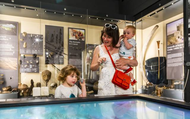 Mother with two children using an interactive display in the museum