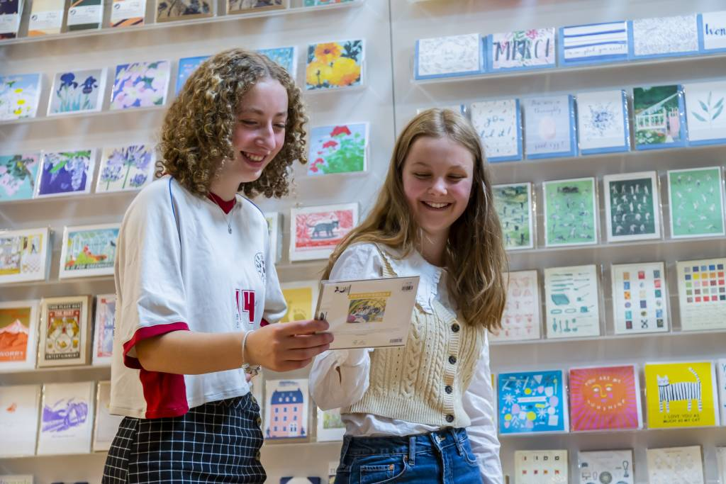 Two teenage girls looking at a greetings card and smiling.
