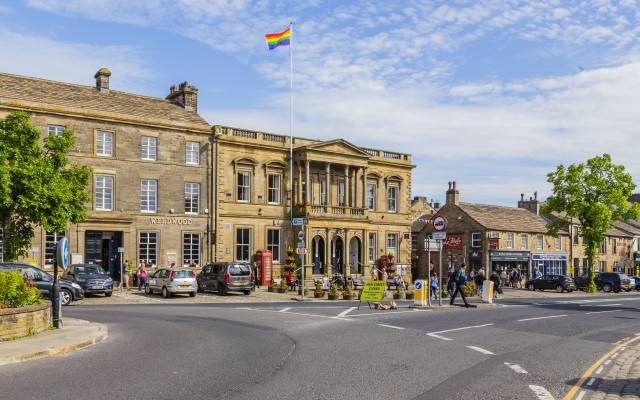 An exterior view of Skipton Town Hall with a rainbow pride flag flying on the flagpole.