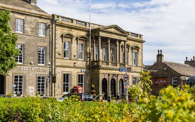 The extertior of Skipton Town Hall. Stone building with cgreen bush in the forground.