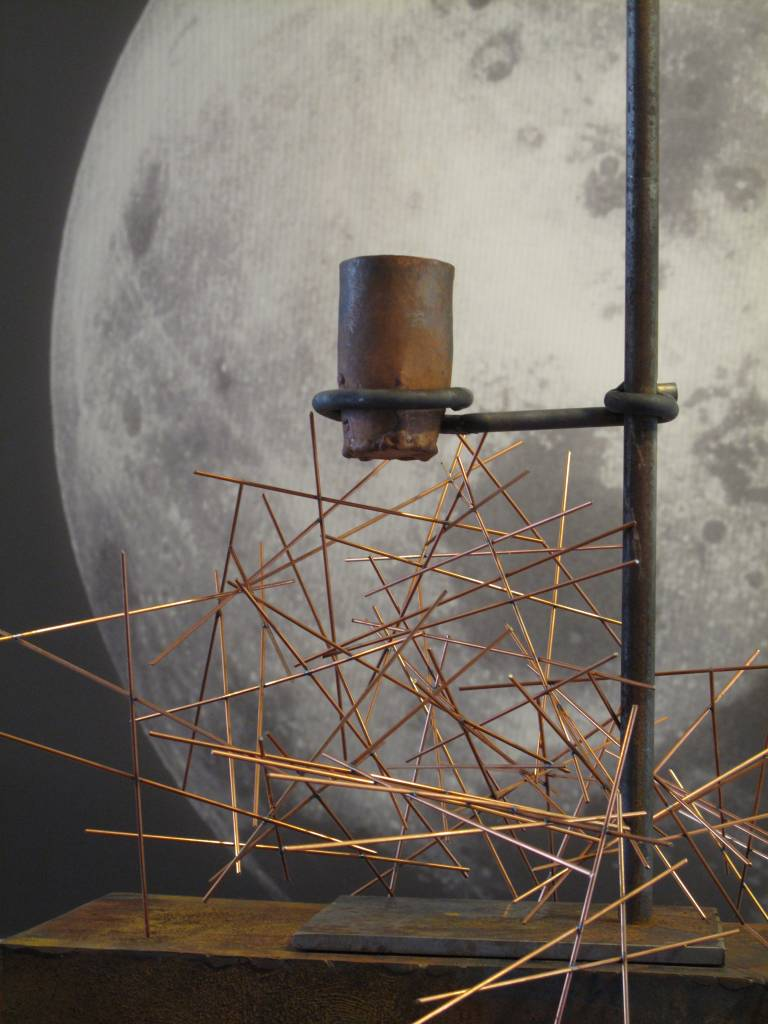 Sculpture with copper rods and image of the moon in the background