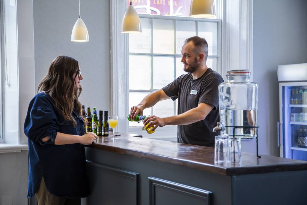 a man serves a drink to a woman at a bar